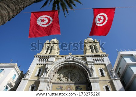Cathedral of St Vincent de Paul with national Tunisian flags on the  Avenue Habib Bourguiba in Tunis,Tunisia. - stock photo