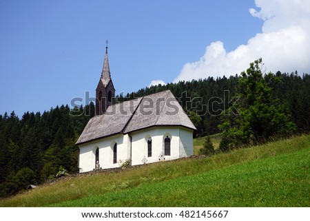 Catholic church on the grass at the forest