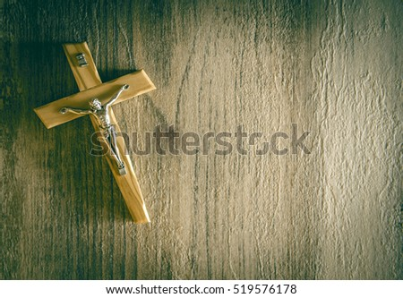 Catholic crucifix on a wooden background. Selective focus. LOMO effect