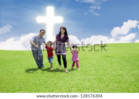 Catholic family is having fun by the Cross in the park - stock photo