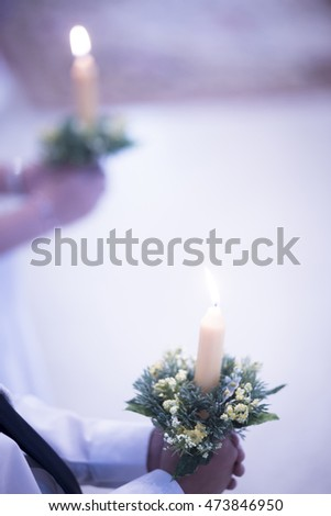 Catholic first communion religious ceremony boy in white shirt holding candle in church.