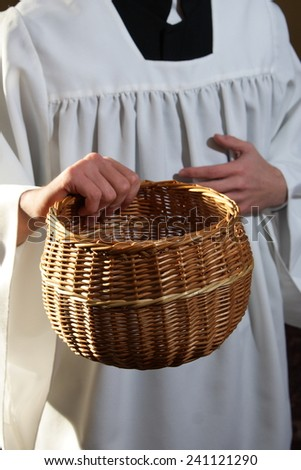 Catholic priest collects money for the church - stock photo