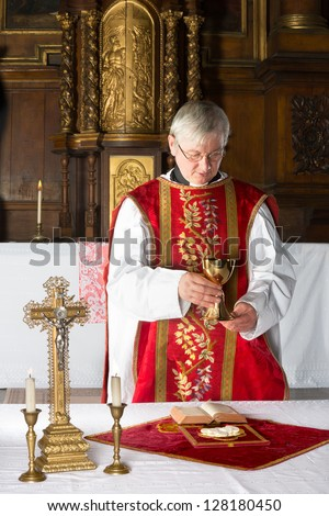 Catholic priest during consecration in a medieval church with 17th century interior - stock photo