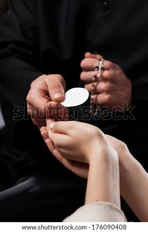 Catholic priest giving beliver a Holy Communion  - stock photo