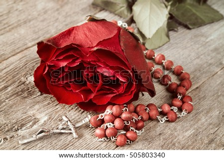 Catholic rosary and red rose on old wooden background