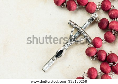 Catholic rosary on old paper background with copy-space - stock photo