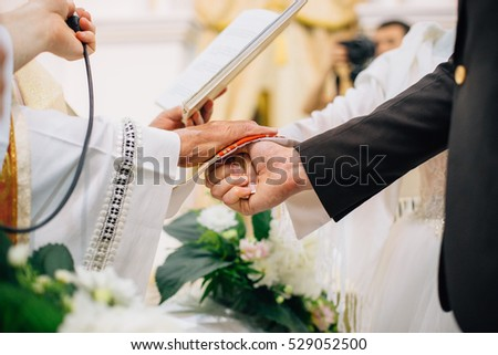 Catholic wedding ceremony hand priest on stock photo royalty free catholic wedding ceremony hand of priest on bride and groom hands junglespirit Image collections