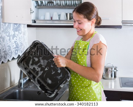 caucasian adult brunette washing kitchenware indoors