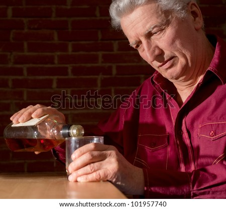 Caucasian adult male with a nice bottle sitting on a dark background - stock photo