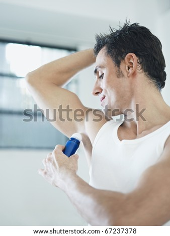 caucasian adult man applying stick deodorant. Vertical shape, waist up, copy space - stock photo