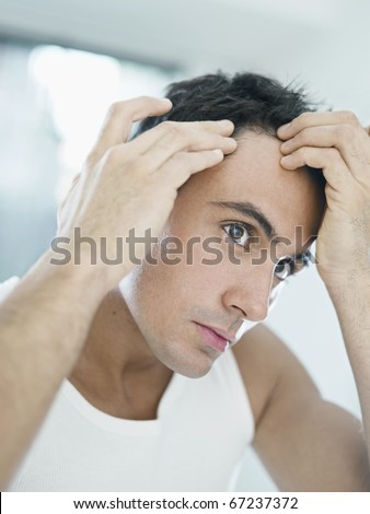 caucasian adult man checking hairline. Vertical shape, head and shoulders - stock photo