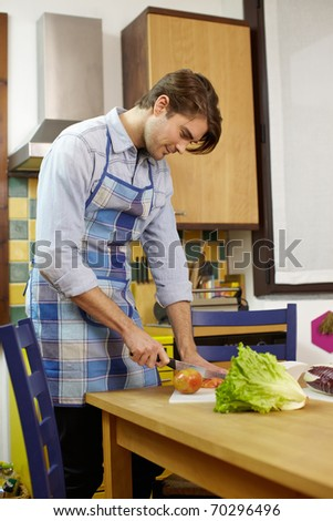 caucasian adult man cutting vegetables in kitchen. Vertical shape, side view