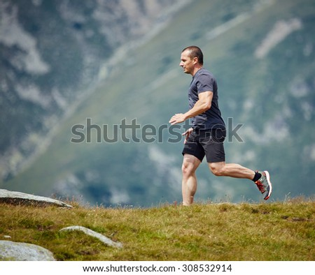 Caucasian athlete trail running in the mountains, ultramarathon - stock photo