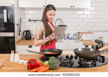 Caucasian attractive woman with tablet in the kitchen.