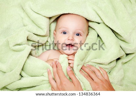 Caucasian baby boy covered with green towel joyfully smiles at camera with mother's hands on him - stock photo