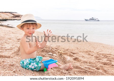 Caucasian baby (boy) is sitting at the beach. Cute child is playing with toys and shellfishes (muscle-fish) on the sand in summer day. Copyspace, close up, outdoor (Sharm El Sheikh, Egypt).   - stock photo