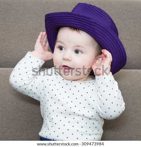 Caucasian baby boy weared a hat sitting on braun sofa at home - stock photo