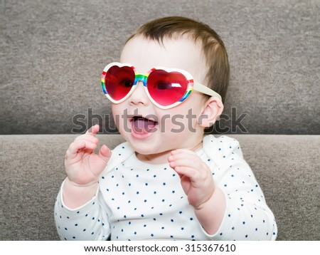 Caucasian baby boy weared a hat sitting on brownn sofa at home - stock photo