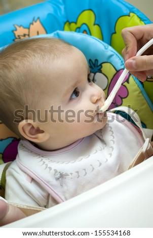 Caucasian baby girl feeding herself - stock photo
