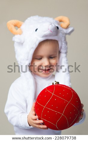 Caucasian baby toddler wearing a sheep hat with yellow horns and white shirt standing on light background holding red golden chinese ornament decoration, New Year 2015 concept, studio. Selective focus - stock photo