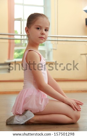 Caucasian ballerina warming up in pointe in the ballet hall on the wooden dance floor - stock photo
