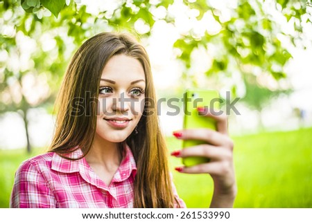 Caucasian beautiful girl look at camera against fresh spring green grass and leaves of summer trees background Close up portrait of Young adult woman using green mobile cell phone in central city park - stock photo