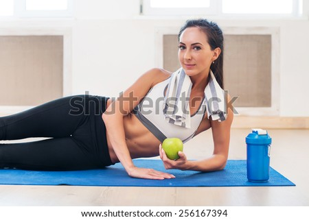 Caucasian beautiful healthy athletic sportive girl with green apple and Yoga Mat and shaker - stock photo