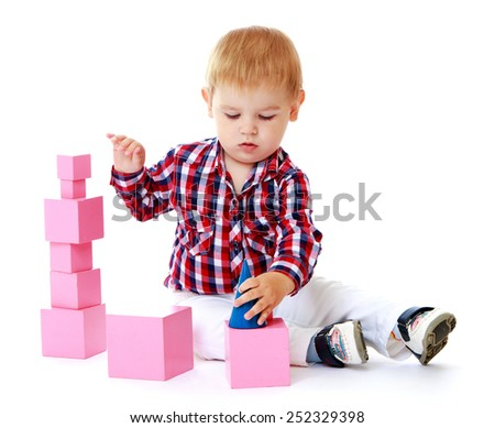 Caucasian beautiful little boy sitting on the floor and adds cubes.Isolated on white background, Lotus Children's Center. - stock photo