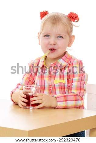 Caucasian beautiful little girl drinking juice from a glass.Isolated on white background, Lotus Children's Center. - stock photo