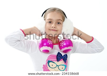 Caucasian beautiful little girl holding a Christmas decorative pink balls for Christmas tree decoration / Smiley girl holding pink decorative balls - stock photo