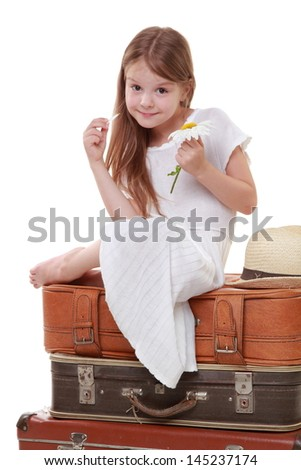 Caucasian beautiful little girl in a white dress and hat sits on the three old suitcases isolated on white - stock photo