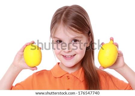 caucasian beautiful little girl with fresh yellow lemons. - stock photo