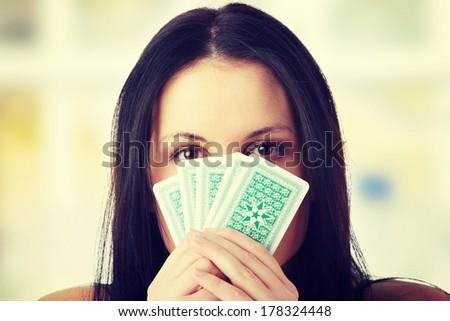 Caucasian beauty playing strip poker - stock photo