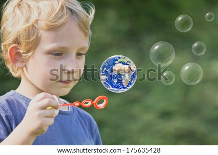 Caucasian blond boy is playing with soap bubbles. One of these bubbles is Earth globe.  - stock photo