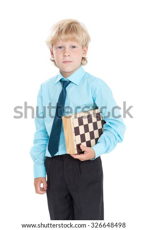 Caucasian blond schoolboy in blue shirt holding chess board in his hands, isolated on white background - stock photo