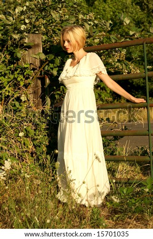 Caucasian blond woman leaning against a steel gate, wearing a vintage dress.
