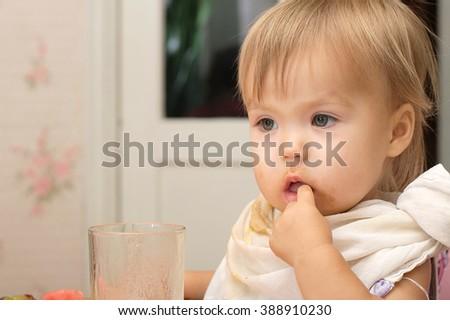 Caucasian blonde little girl eating portrait thinking satiate - stock photo