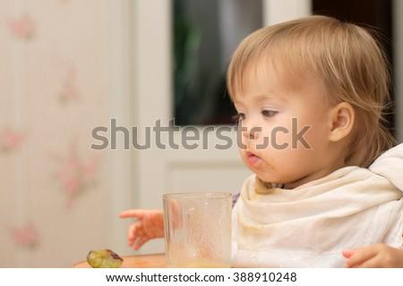 Caucasian blonde little girl eating sitting on high chair - stock photo
