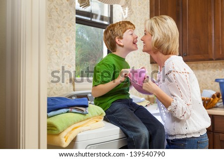 Caucasian blonde mother and red headed son doing laundry in laundry room, while looking at each other - stock photo