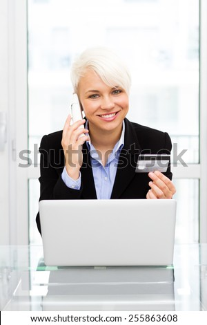 Caucasian blonde woman is online shopping with credit card and phone in office - stock photo