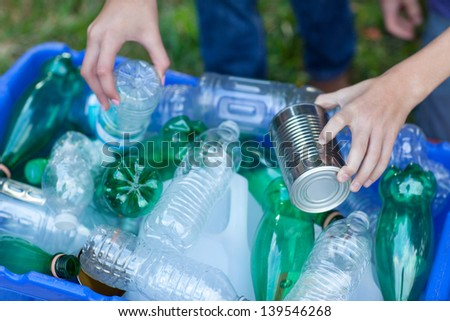 Caucasian boy and girl putting clear and green bottles and metal cans in recycling blue bin outside in yard - stock photo