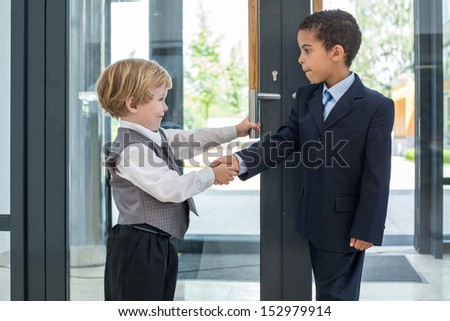 Caucasian boy and mulatto boy in business clothes greeting each other in a business center - stock photo