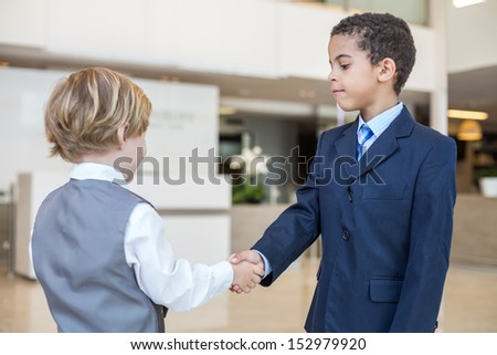 Caucasian boy and mulatto boy in business clothes shake hands in a business center - stock photo