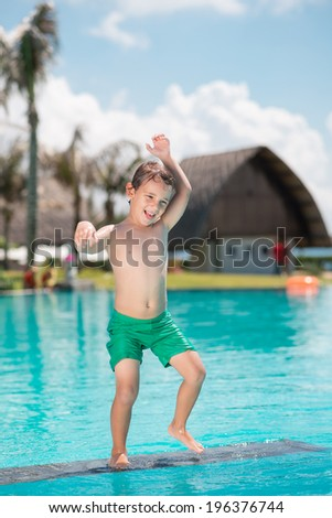Caucasian boy dancing while standing in the swimming pool - stock photo