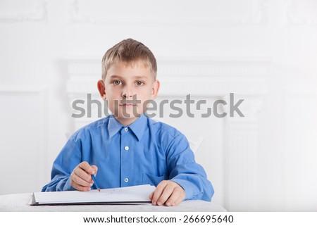 caucasian boy draws a pencil on the album - stock photo