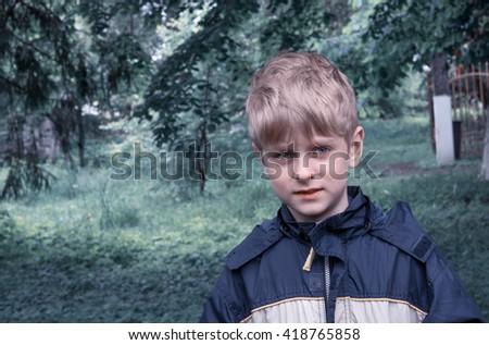 caucasian boy in blue waterproof raincoat - stock photo