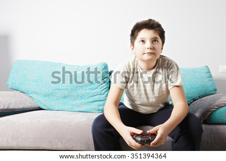 Caucasian boy playing video game while sitting on couch - stock photo