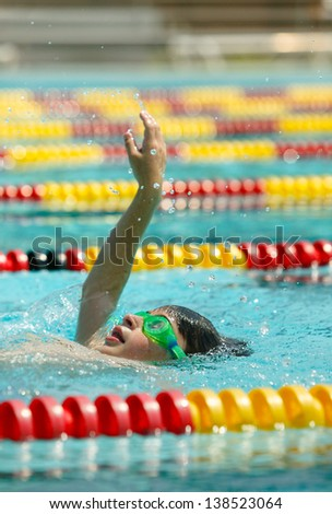 Caucasian Boy practices his backstroke swimming in lap pool with red and yellow lane markers. - stock photo