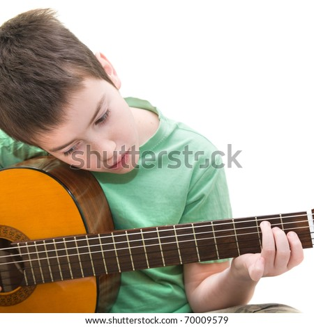 caucasian boy practicing; playing acoustic guitar; isolated on white background; - stock photo