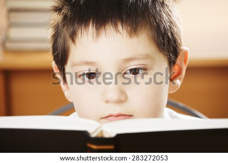 Caucasian boy reading big book closeup photo